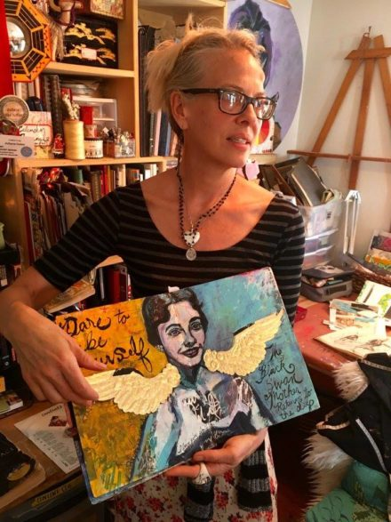 Juliana Coles holding journal featuring painting of her mom